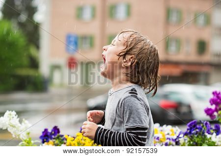Cute little boy playing under the rain outdoors, catching rain drops by his mouth
