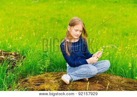 Cute little girl of 7 years old playing in a forest, picking wildflowers