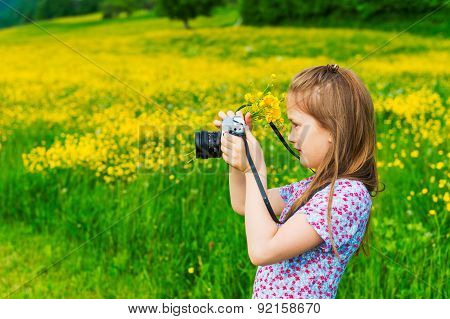 Cute little girl taking pictures of the nature