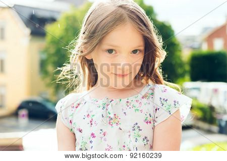 Outdoor close up portrait of a cute little girl under the rain in summertime