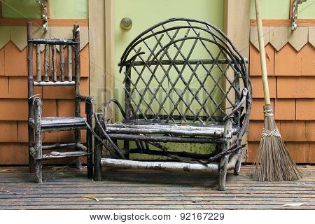 Small child size chair and loveseat made from tree branches on an wood porch.