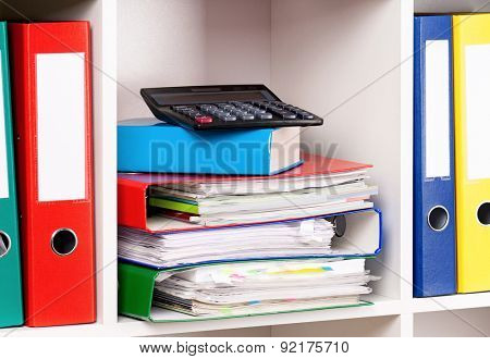 File folders and calculator on the shelves at office