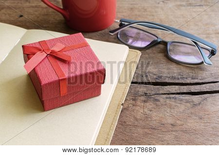 Red Gift Box With Notebook And Cup Of Coffee