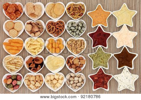Crisp and dip party food selection in heart and star shaped porcelain bowls over bamboo background.