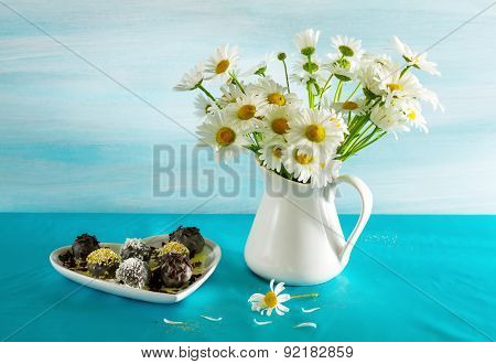 Still life with camomiles and chocolates.