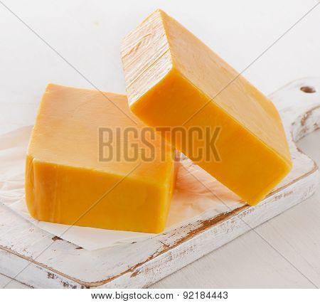 Cheddar Cheese On A White Cutting Board.