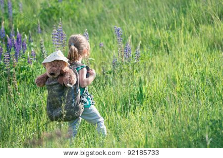 Girl With Teddy Bear In Backpack In Tall Grass
