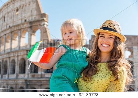 Smiling Mother And Daughter Waving Italian Flag By Colosseum