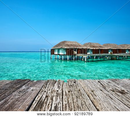 Beautiful beach with water bungalows and old wooden pier at Maldives