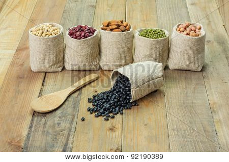 Different Kinds Of Beans In Sacks Bag, Focus On Scattered Black Beans