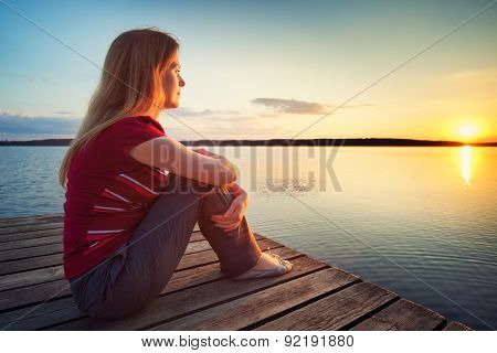 Young woman in casual clothing sitting on wooden bridge and looking on sunset over lake.
