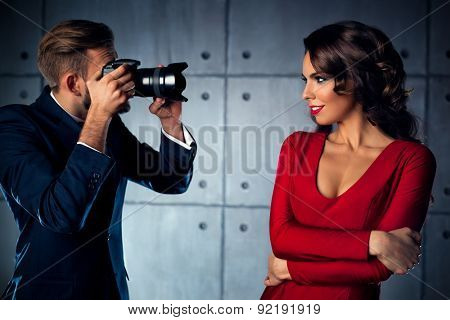 Young woman in red dress posing to man photographer. Elegant evening clothing.
