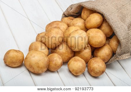 New Potatoes In A Bag On A White Wooden Background