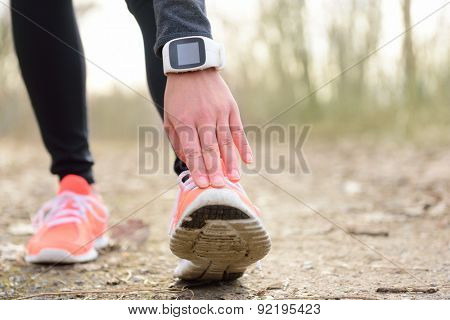 Runner stretching leg before run. Closeup of running shoes of a female jogger touching toe wearing a wearable tech - sportswatch activity tracker or smartwatch used as a heart rate monitor for cardio.