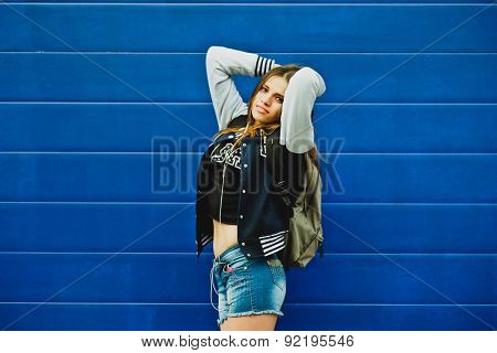 Happy young girl listening music  in headphones over blue wall background