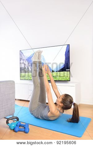 Home fitness ab workout in front of television. Girl doing toe touch exercises to train upper abs while watching a nature TV show or training program living a healthy life.