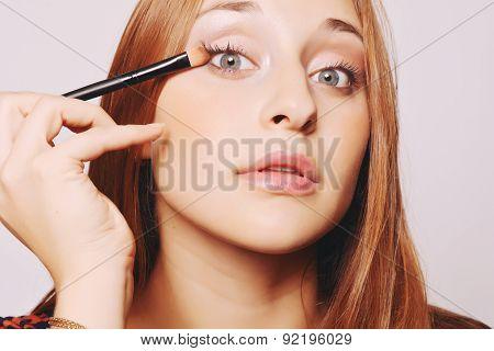 Beautiful Young Woman Applying Make Up.