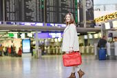 pic of board-walk  - Young woman at international airport checking electronic board and waiting for her flight - JPG