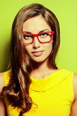 picture of spectacles  - Beauty portrait of a positive young woman in spectacles and bright yellow dress over green background - JPG