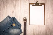 pic of no clothes  - many jean clothes and shoes on wood background - JPG
