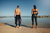 Постер, плакат: Young Athletes Standing On Beach Preparing For Triathlon