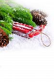 stock photo of sled  - Decorative sled on snow with fir tree branches on white background - JPG