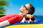foto of sunbather  - jack russell dog and owner sunbathing a having a siesta under a palm tree on summer vacation holidays at the beach - JPG