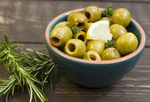 picture of kalamata olives  - A bowl of olive on a wooden board with rosemary