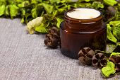 foto of sackcloth  - Natural skin care cream in open jar of dark glass surrounded by green leaves on sackcloth surface - JPG