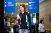 stock photo of terminator  - Portrait of smiling young woman in 20s with backpack waiting for flight in modern airport terminal using cell phone app in public wifi area texting blurred electronic panel on background - JPG