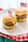 stock photo of beef-burger  - Mini beef burgers with American flag in white plateselective focus - JPG