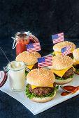 stock photo of beef-burger  - Mini beef burgers with American flagselective focus - JPG