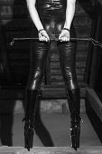 foto of latex woman  - Sexy woman body in latex catsuit dominatrix holding whip in barn black and white bdsm - JPG