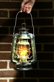 stock photo of kerosene lamp  - Hand holding kerosene lamp on brick wall background - JPG