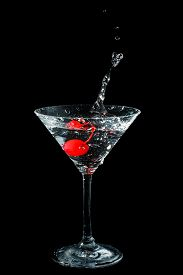 stock photo of black-cherry  - Maraschino cherry dropped in cocktail glass with fluid isolated on black - JPG