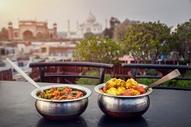 stock photo of indian  - Aloo Gobi and Sabji Masala Traditional Indian food in metal plates on rooftop restaurant with Taj Mahal view in Agra Uttar Pradesh India - JPG