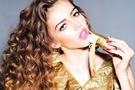 stock photo of denude  - Portrait of alluring young girl with curly hair in gold jacket holding and eating golden banana looking forward standing on grey background horizontal picture - JPG