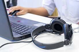 stock photo of production  - Man hand using keyboard and mouse to control laptop with headphone beside working in music editing studio production - JPG