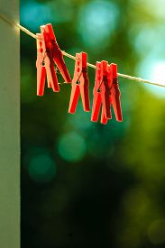 image of pegging  - Red clips for washing laundry clothes pegs on string rope outdoor - JPG