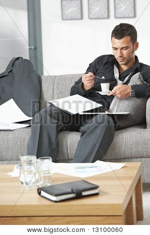 People at office. Tired businessman sitting on sofa looking at documents drinking coffee.