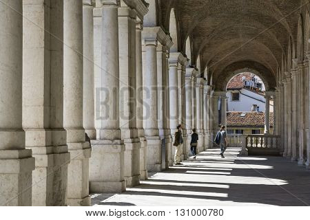 VICENZA,ITALY-APRIL 3,2015:people on the famous colonnade of the Palladian basilica in the center of Vicenza during a sunny day.