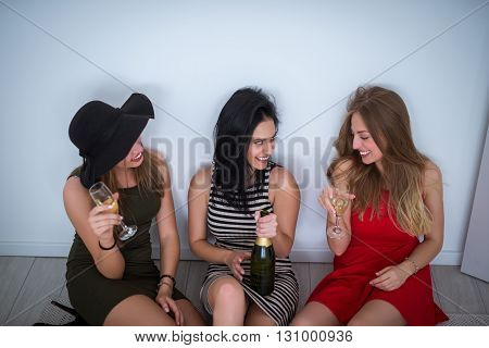 Drunk girls sitting on the floor and drinking a wine.