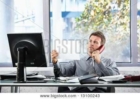 Smiling professional businessman on landline call looking at paper held in hand siting at office desk.