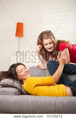 Teen girls listening music together on earphones at home, looking at camera smiling.