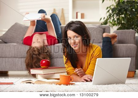 Teenage girls learning together at home with books and laptop, girl in front smiling at camera.