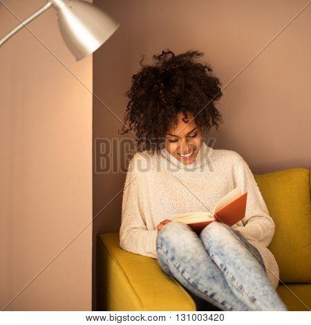 Beautiful african american girl reading a book.