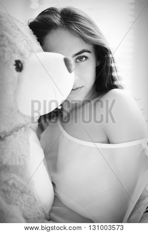 sensual girl sitting with teddy bear monochrome blurred image
