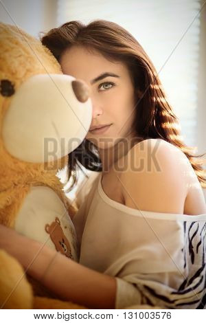 sensual girl sitting with teddy bear toned blurred image