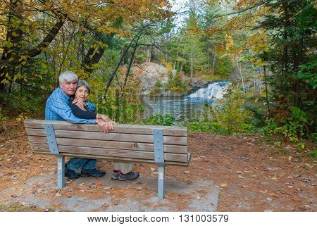 Elderly couple sitting on a bench on the background of a waterfall Marinette county Wisconsin