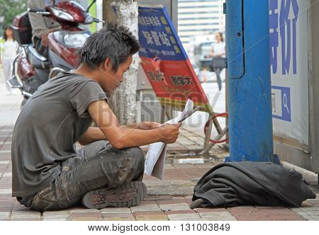 Guy In The Dirty Clothes Is Reading Newspaper On Street In Kunming